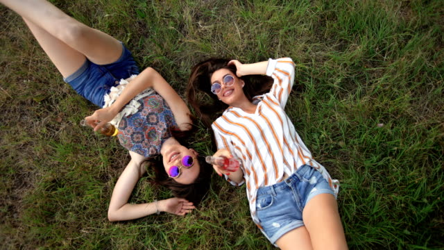 Two women drinking and playing in meadow