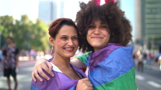 Two women embracing holding rainbow flag during LGBTQI parade Two women embracing holding rainbow flag during LGBTQI parade lgbtqi rights stock videos & royalty-free footage
