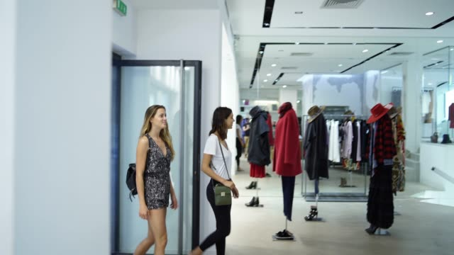 Two women entering a clothing store