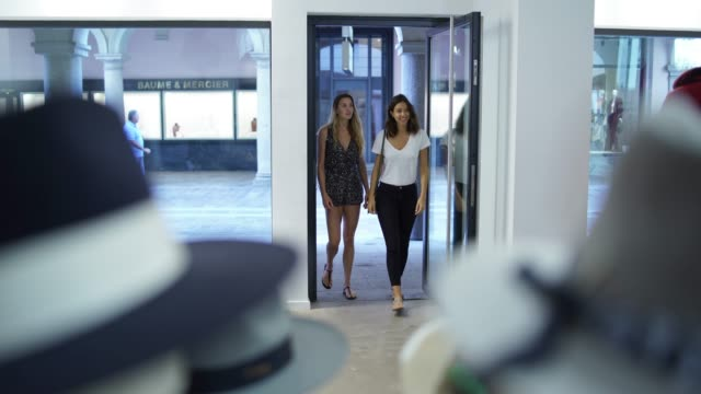 vídeos de stock e filmes b-roll de two women entering a clothing store - store