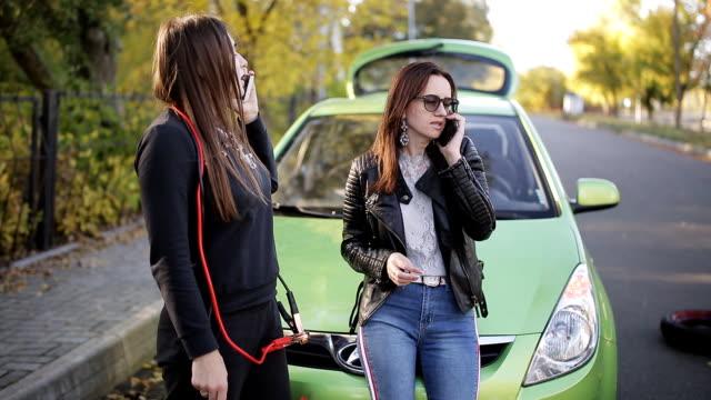vídeos de stock e filmes b-roll de two women girl calling cellphone near her broken car. two women standing near broken car on the road. - berma da estrada