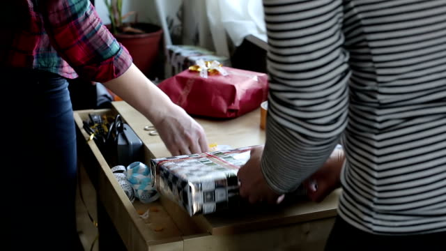 Two women hands are packing gift Two women hands are packing gift boxes. wrapped stock videos & royalty-free footage