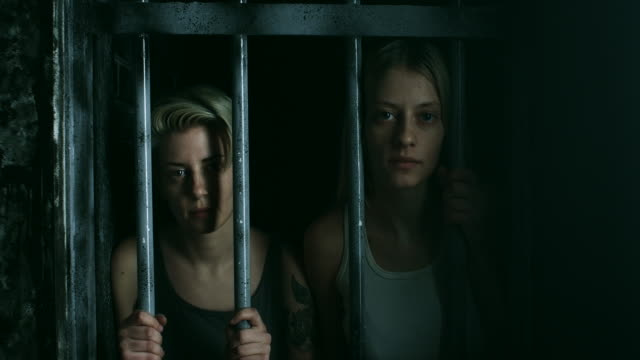 Two women holding bars and looking through at prison cell video