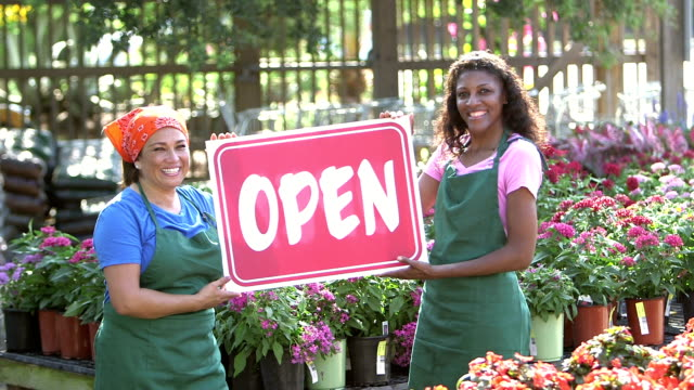 two women holding open sign in plant nursery - open sign stock videos & royalty-free footage