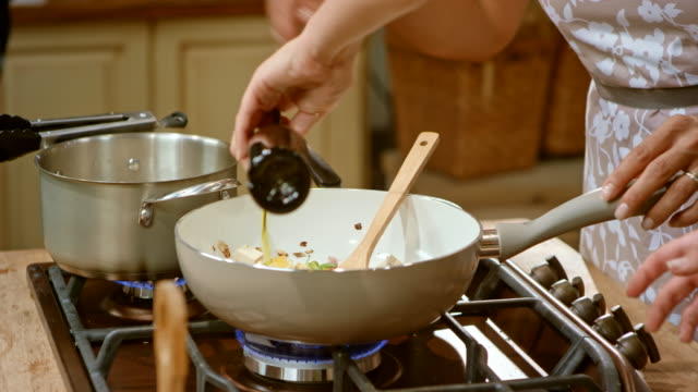 ld two women in a cooking show preparing a dish, pouring olive oil and stirring the vegetables - olio d'oliva video stock e b–roll
