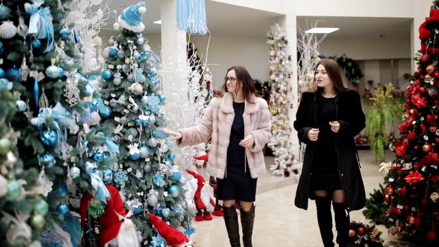 店裡的兩位女士在耶誕節時選擇聖誕裝飾品作為節日禮物。 - 人造的 個影片檔及 b 捲影像