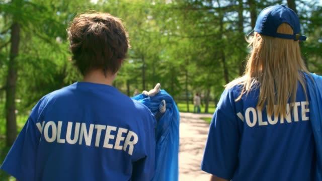due donne in t-shirt da volontariato - dorso umano video stock e b–roll