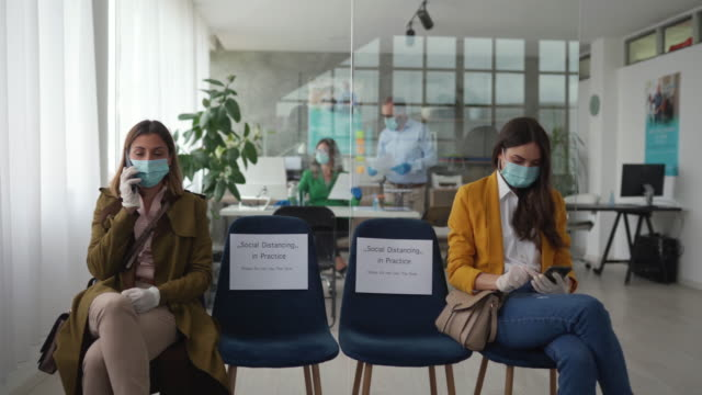 vídeos de stock, filmes e b-roll de duas mulheres mantêm distanciamento social na sala de espera do banco - dia do cliente