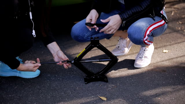 Two women know how to operate the Jack to change a punctured wheel of the car.