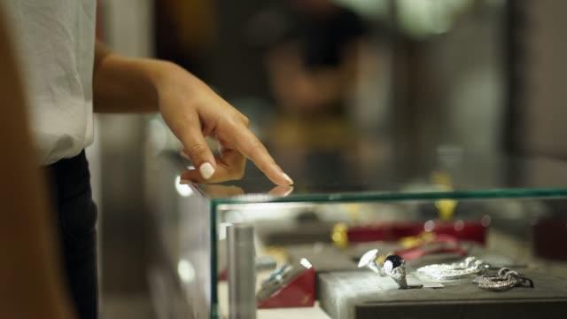 vidéos et rushes de deux femmes à la recherche et le pointant à bijoux derrière un cas - joaillerie