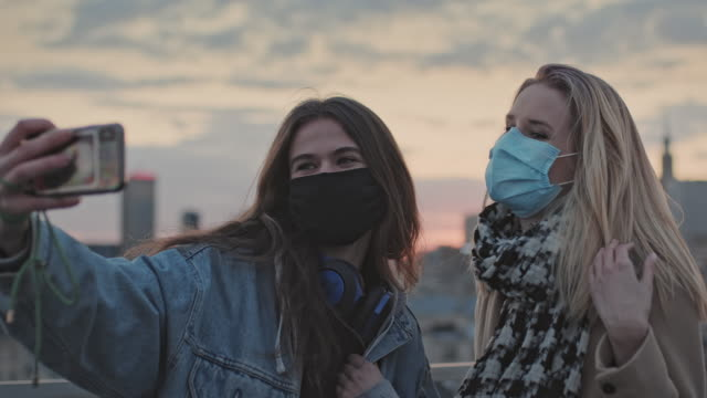 Two women making selfie on a roof. City sunset during pandemic video