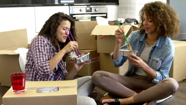 Two Women Moving Into New Home Enjoying Takeaway Meal video