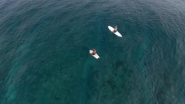 Two women on surfboard in ocean Two women on surfboard in ocean indian ocean islands stock videos & royalty-free footage
