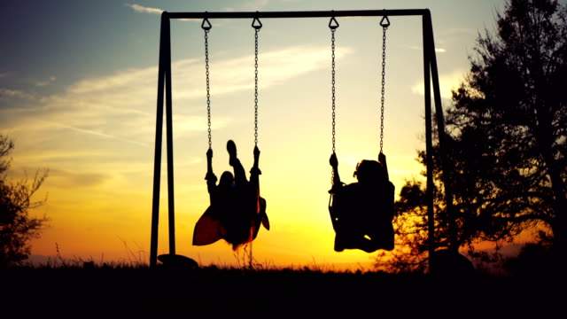 two women on swing looking at sunset - altalena video stock e b–roll
