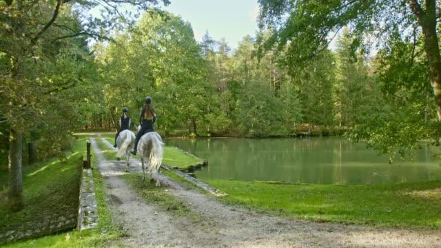 CS Two women on trotting white horses crossing lake bridge