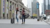 istock Two women on vacation walking on city sidewalk 1218659355