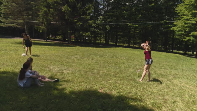 Two women playing badminton on the lawn, and their daughters watching the game. Top view directly above, aerial drone video video