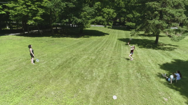 two women playing badminton on the lawn, and their daughters watching the game. top view directly above, aerial drone video - badminton stock videos & royalty-free footage