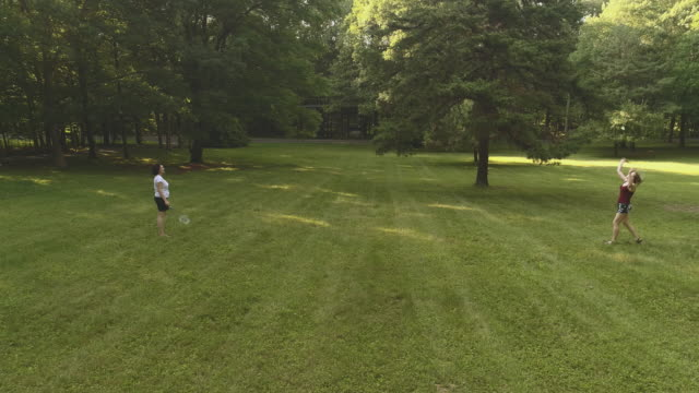 Two women playing badminton on the lawn. Low altitude aerial drone video video