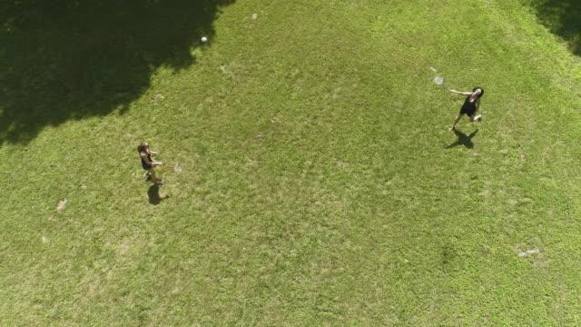 Deux femmes, jouer au badminton sur la pelouse. Fille d'adolescent ce qui porte le chapeau à sa mère. Vue de dessus directement au-dessus, vidéo aérienne drone - Vidéo