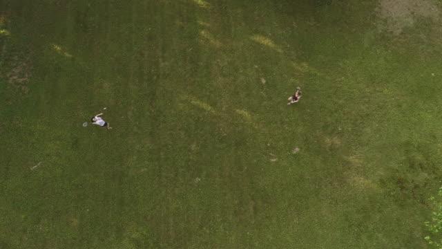 2 人の女性は、芝生でバドミントンを再生します。真上、空中ドローン ビデオ トップ ビュー - スポーツ バドミントン点の映像素材/bロール