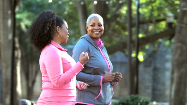 two women power walking in the city, talking and smiling - amicizia tra donne video stock e b–roll