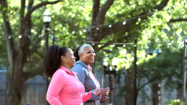 Two women power walking in the city, talking and smiling Two African-American women power walking together in the city, along a tree-lined street, smiling and talking. The senior woman in pink is in her 60s. Her friend is a mature woman in her 50s. healthy lifestyle stock videos & royalty-free footage