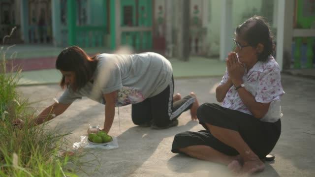 Two women praying their ancestor at qingming festival