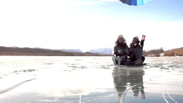 Two women relax on frozen pond, release umbrella