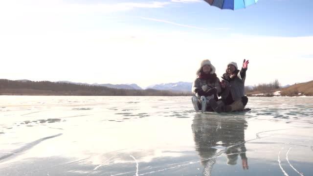 vídeos de stock e filmes b-roll de two women relax on frozen pond, release umbrella - skate liberdade gorro