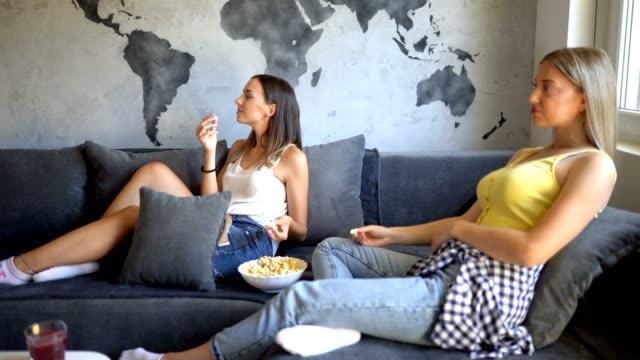 vídeos de stock e filmes b-roll de two women relaxing on sofa in the living room - concrete wall interior