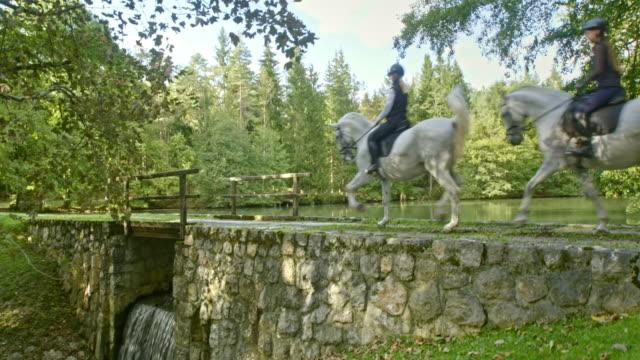 CS Two women riding their white horses over a bridge