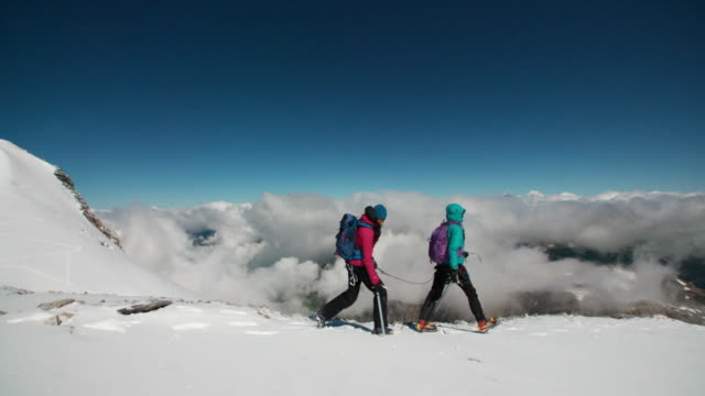 Two women roped together trekking across a windy glacier together Two adult women with ice axes roped together traverse a glacier. guidance stock videos & royalty-free footage