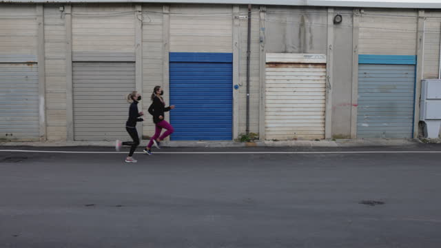 Two women running and training with face masks video