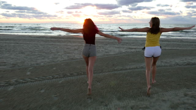 Two women running towards the sea on the beach at sunrise video