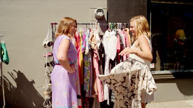 vídeos de stock, filmes e b-roll de duas mulheres comprando para roupas em um mercado ao ar livre - arméria