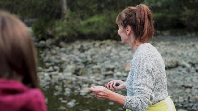 湖に石をスキミングする二人の女性 - 日常から抜け出す点の映像素材/bロール