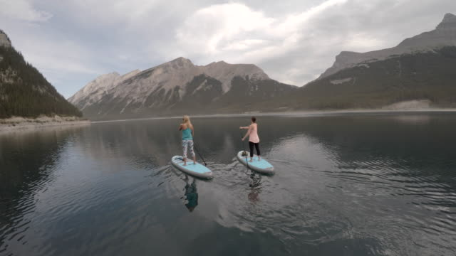 Two women stand up paddle boarding on alpine lake  pedal pushers stock videos & royalty-free footage