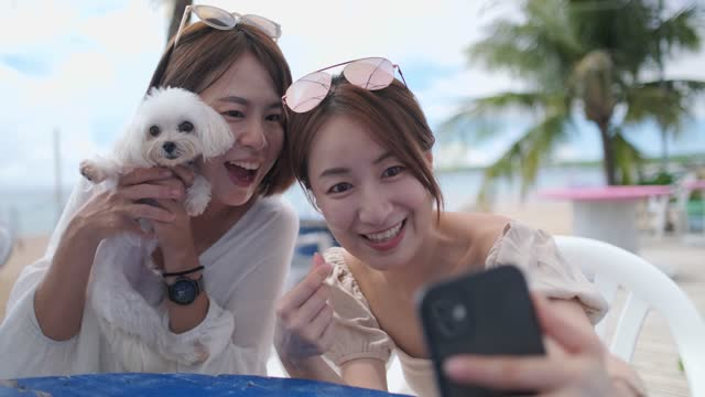 Two women taking selfies with smartphones