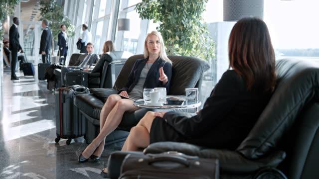 stockvideo's en b-roll-footage met ds twee vrouwen praten in de business lounge op de luchthaven - vliegveld vertrekhal