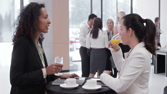 말하는 회의 홀의 로비에서 커피를 마시는 동안 두 여자 - 10초 이상 스톡 비디오 및 b-롤 화면