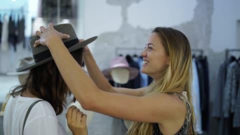 vidéos et rushes de deux femmes essayer des chapeaux dans un magasin de vêtements - chapeau