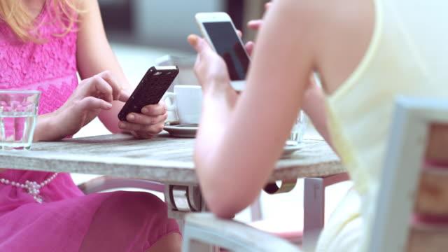 Duas mulheres usando telefones enquanto tomando café em dia ensolarado - vídeo