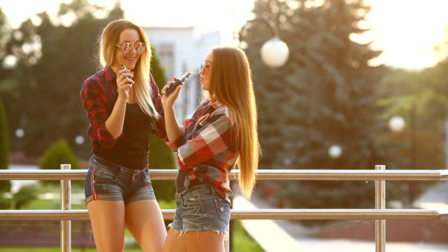 Two women vaping outdoor. The evening sunset over the city. Toned image video