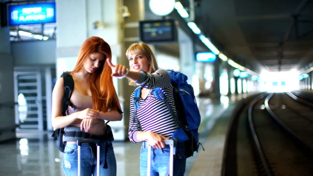 Two women waiting for a train.