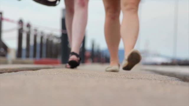 Two Women Walking along a Marina, Just Feet video