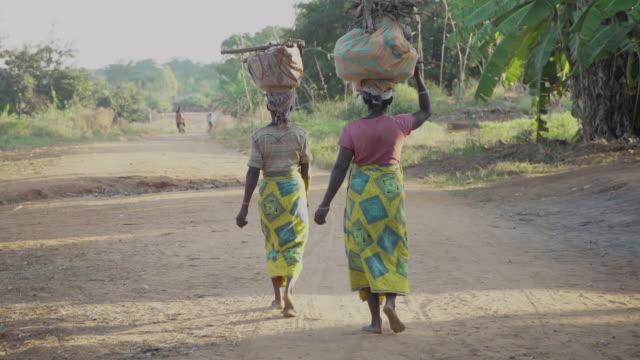 vídeos y material grabado en eventos de stock de dos mujeres caminando por camino de tierra en la aldea africana - aldea