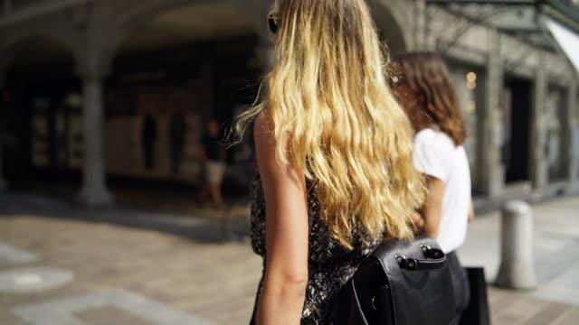 två kvinnor går ut ur en butik till en plaza bakifrån - kameraåkning på räls bildbanksvideor och videomaterial från bakom kulisserna