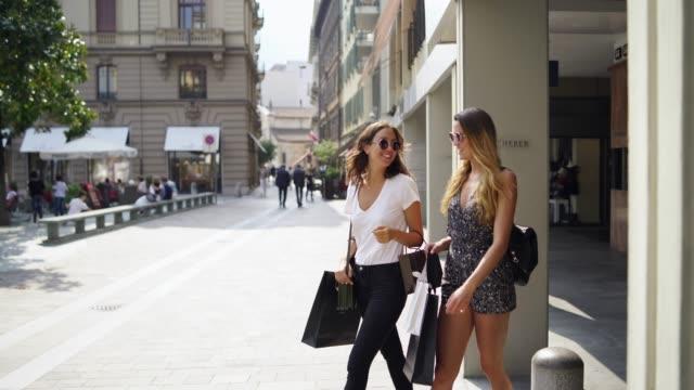två kvinnor går ut ur en butik till en plaza framifrån - spendera pengar bildbanksvideor och videomaterial från bakom kulisserna