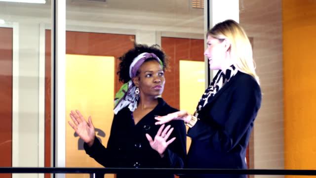 Two women walking, talking in office hallway